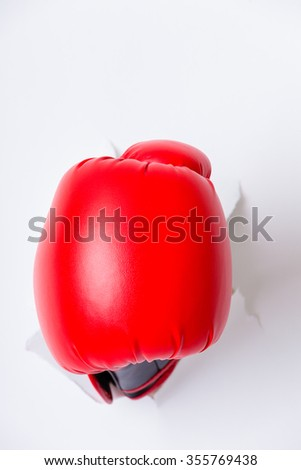 Hand in boxing glove through paper hole - stock photo