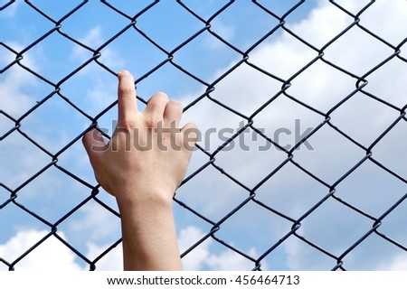 hand in cage with blue sky background, prisoner in the jail, wait for freedom