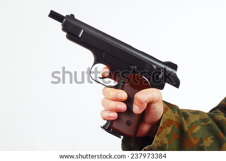 Hand in camouflage uniform with discharged gun on a white background - stock photo