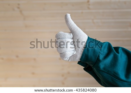 Hand in clean white fabric gloves thumbs up on tongue and groove wooden planks background - stock photo