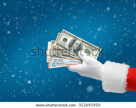 Hand in costume Santa Claus is giving money / studio shot of man's hand holding dollars and euros banknotes / Merry Christmas & New Year's Eve concept / Closeup on blurred blue background. - stock photo