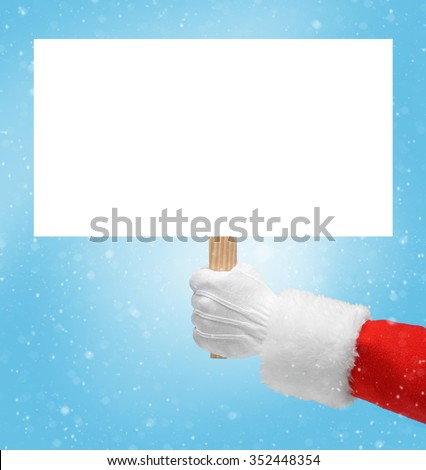 Hand in costume Santa Claus is holding empty board / studio shot of man's hand holding empty blank / Merry Christmas & New Year's Eve concept / Closeup on blurred blue background. - stock photo