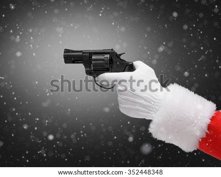 Hand in costume Santa Claus is holding gun / studio shot of man's hand holding loaded gun / Merry Christmas & New Year's Eve concept / Closeup on dark black background. - stock photo