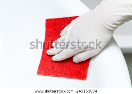 Hand in glove cleans washbasin red sponge - stock photo