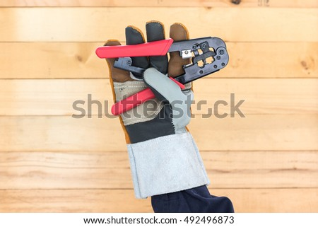 Hand in glove holding a wire stripper tool with wall wood background