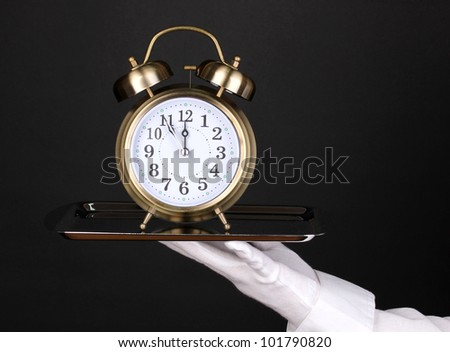 Hand in glove holding silver tray with alarm clock isolated on black