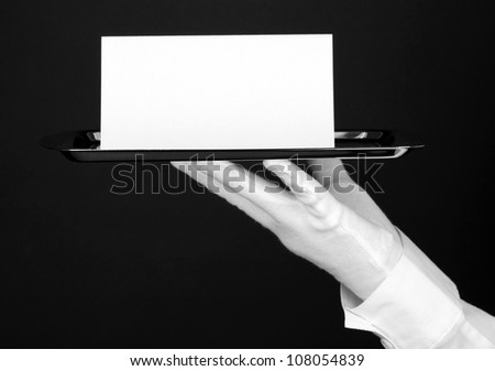 Hand in glove holding silver tray with blank card isolated on black