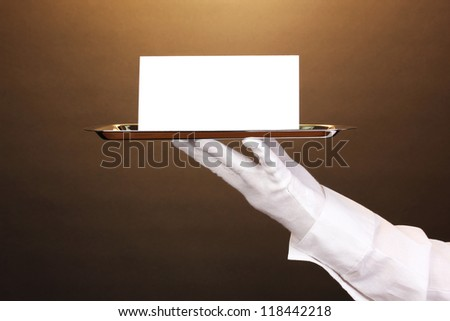 Hand in glove holding silver tray with blank card on brown background