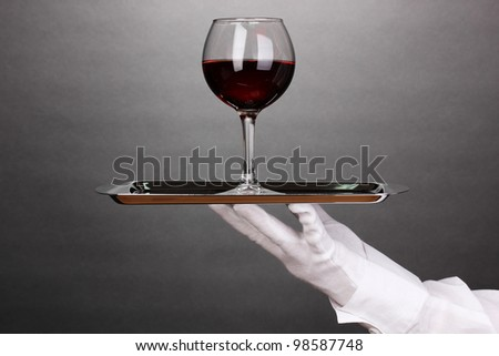Hand in glove holding silver tray with wineglass on grey background - stock photo