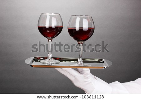 Hand in glove holding silver tray with wineglasses on grey background - stock photo
