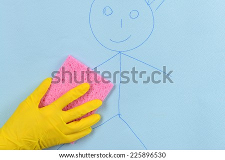 Hand in glove wiping children drawing on wallpaper - stock photo
