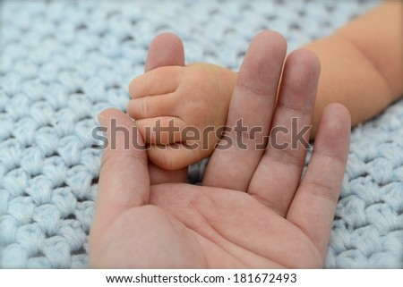 Hand in hand (An infant's hand holding on an adult's hand