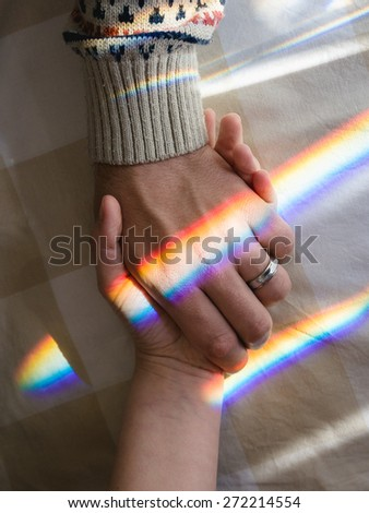 hand in hand with rainbow symbolizing sentimental bond - stock photo