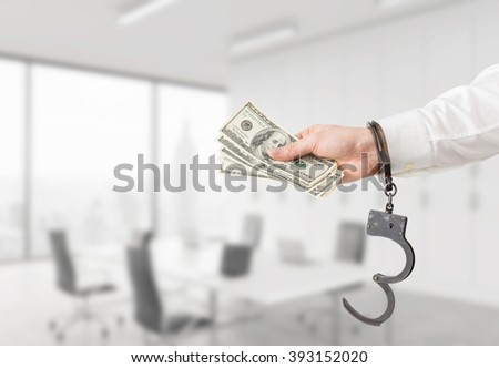 Hand in handcuffs holding money. Blurred office at background. Concept of financial crime. - stock photo