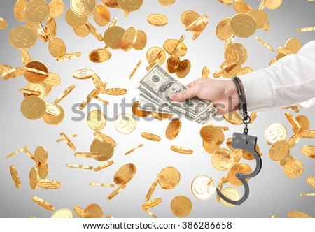 Hand in handcuffs holding money. Golden coins falling at background. Concept of financial crime. - stock photo