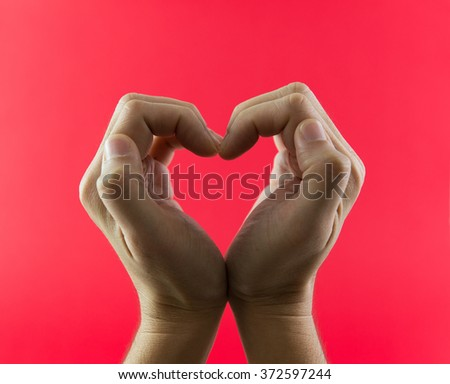 Hand in heart shape against red color background - stock photo