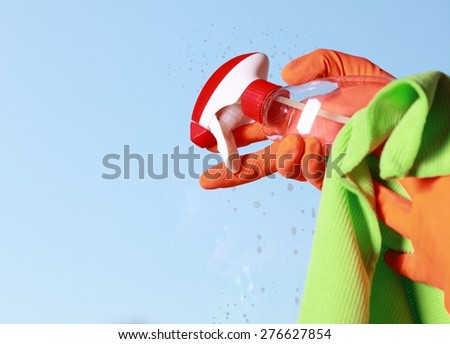 hand in orange glove cleaning window with rag and spray detergent. Spring cleaning concept - stock photo