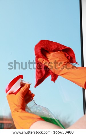hand in orange glove cleaning window with red rag and spray detergent. Spring cleaning concept