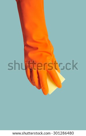 Hand in orange rubber glove with sponge isolated on color background. cleaning - stock photo