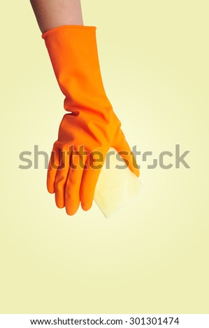 Hand in orange rubber glove with sponge isolated on yellow background. cleaning - stock photo