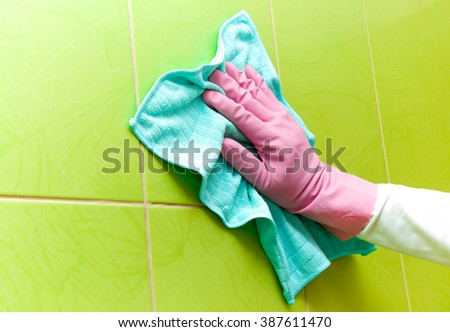 Hand in pink protective glove cleaning tiles with blue rag. Early spring cleaning or regular clean up. Maid cleans house. - stock photo