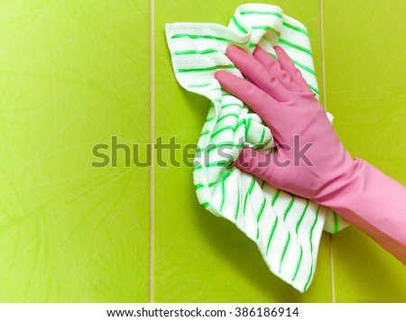 Hand in pink protective glove cleaning tiles with rag. Early spring cleaning or regular clean up. Maid cleans house. - stock photo