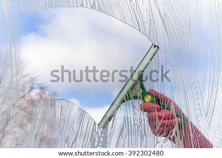 Hand in pink protective glove washing and cleaning window with professionally squeegee on background of cloudy sky .  Early spring windows cleaning. Maid cleans window. - stock photo