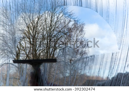 Hand in protective glove washing and cleaning window with professionally squeegee.  Early spring windows cleaning. Maid cleans window. - stock photo