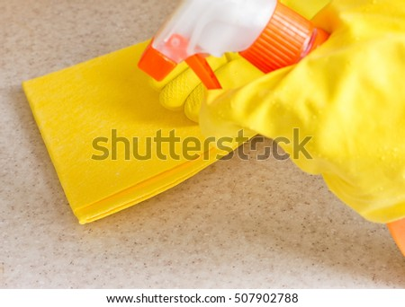 Hand in rubber glove cleans a new kitchen. Woman with housework, cleaning the kitchen.