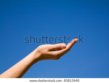 Hand in the form of a handful against the blue sky