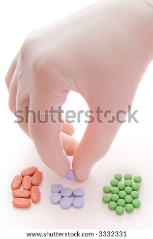 Hand in white glove selecting pills on white