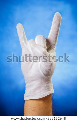 Hand in white glove showing horn sign over blue background - stock photo