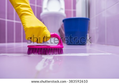 Hand in yellow gloves wash the tile brush. - stock photo