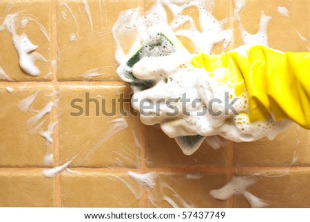 hand in yellow rubber glove holding soapy cleaning sponge - stock photo