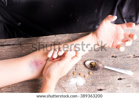 Hand injection drug  with old glass syringe blood, amphetamine tablets and cooked heroin in spoon. on old wood background - stock photo