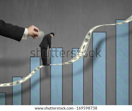 Hand insert coin into businessman back hole which standing on growing money trend with chart on concrete wall background - stock photo