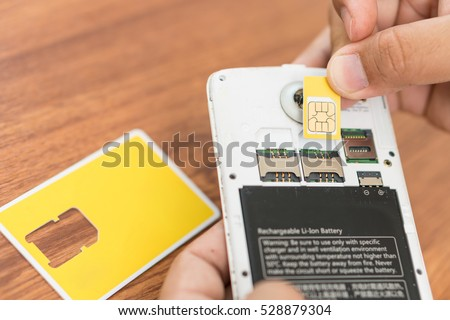 hand insert new sim card with smart phone.