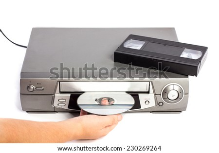 Hand inserting a dvd in to a video recorder and video cassette tape - stock photo