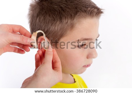 Hand inserting a hearing aid in an ear of a cute boy