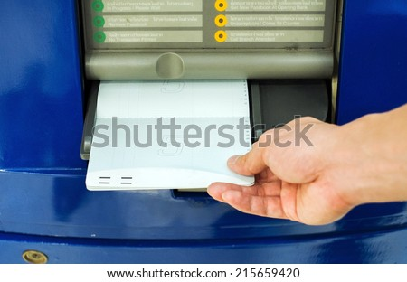 hand inserting account bankbook into automatic passbook update machine