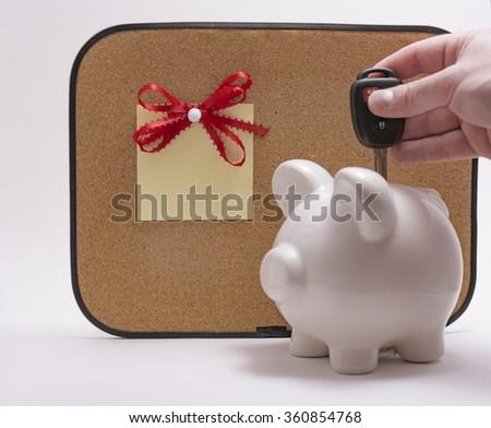 Hand inserting car key in ceramic piggy bank - stock photo