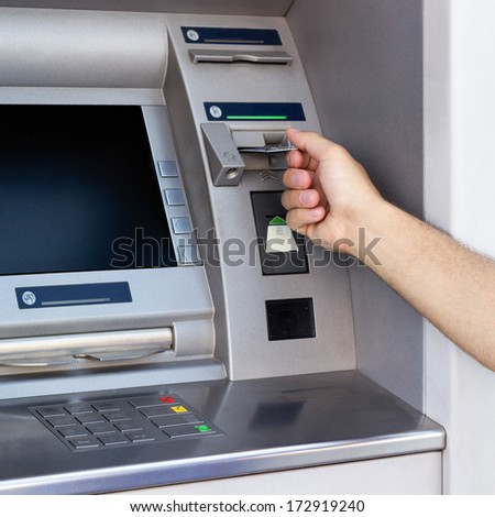 Hand inserting card into cash machine