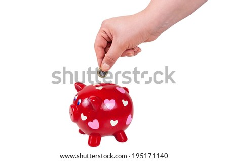 Hand inserting coin into piggy bank isolated on white background with clipping path - stock photo