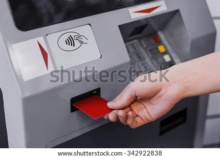Hand inserting credit card into bank machine to withdraw money - stock photo