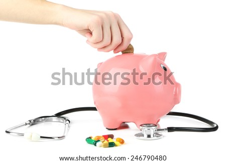 Hand inserting money into pink piggy bank, isolated on white - stock photo
