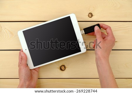 Hand Inserting usb memory stick in tablet   - stock photo