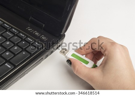 Hand inserting usb memory stick to laptop computer  - stock photo