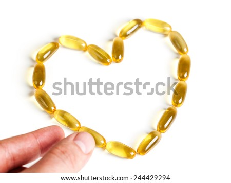 hand is about to pick one of the fish oil capsules on white background. healthy lifestyle concept. - stock photo