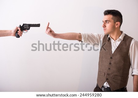 Hand is holding a gun and man with finger up. Grey background. - stock photo