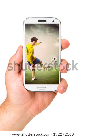 hand is holding a modern phone with soccer or football player shooting a ball on screen - stock photo